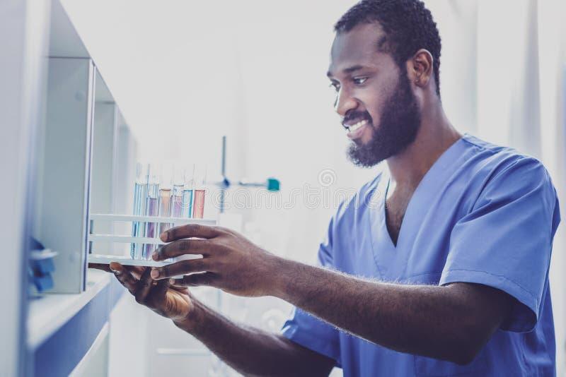 Бородатый биолог в голубой форме устанавливая пробирки стоковая фотография rf