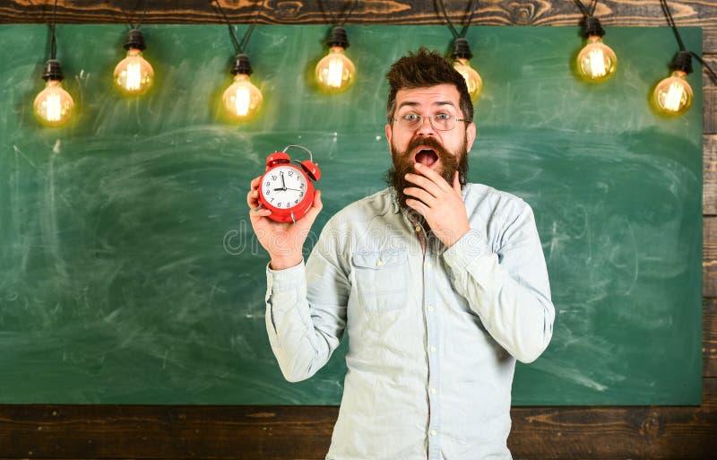 Бородатый битник держит часы, доску на предпосылке, космосе экземпляра Забыл о концепции времени Учитель в eyeglasses стоковые фото