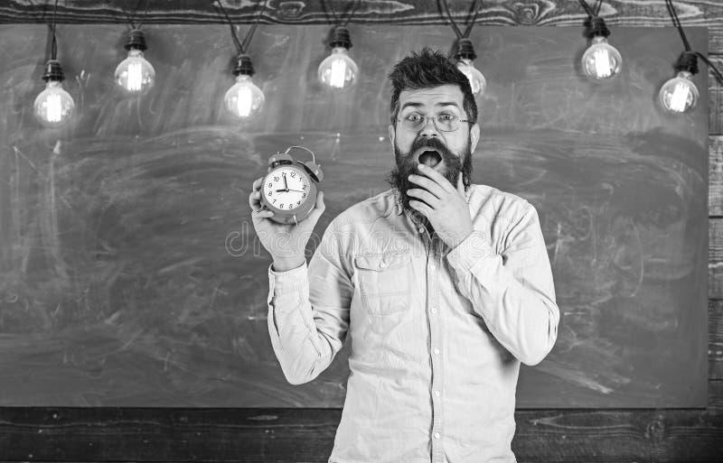 Бородатый битник держит часы, доску на предпосылке, космосе экземпляра Забыл о концепции времени Учитель в eyeglasses стоковые изображения