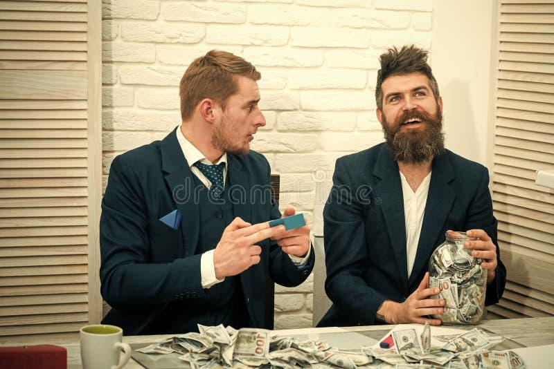 Бородатый босс владения раздражают вполне наличных денег, коллеги держит кредитную карточку Доход от бизнеса, держащ деньги в опа стоковое фото rf