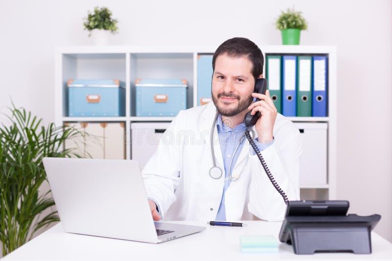 Бородатый доктор работая и зноня по телефону на его офисе Дело, сообщение и медицинская концепция стоковые изображения