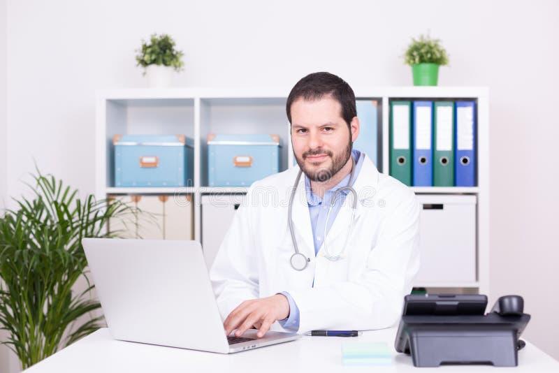 Бородатый доктор работая на его офисе Дело и медицинская концепция стоковое изображение