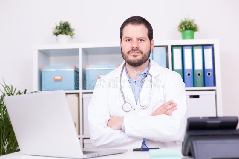 Бородатый доктор работая на его офисе Дело и медицинская концепция стоковая фотография