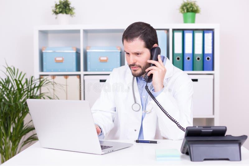 Бородатый доктор работая на его офисе Дело и медицинская концепция стоковые изображения