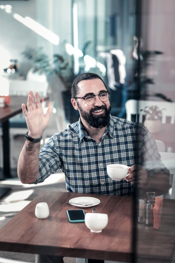 Бородатый испуская лучи человек поднимая его коллеги встречи руки в кафе стоковое изображение rf