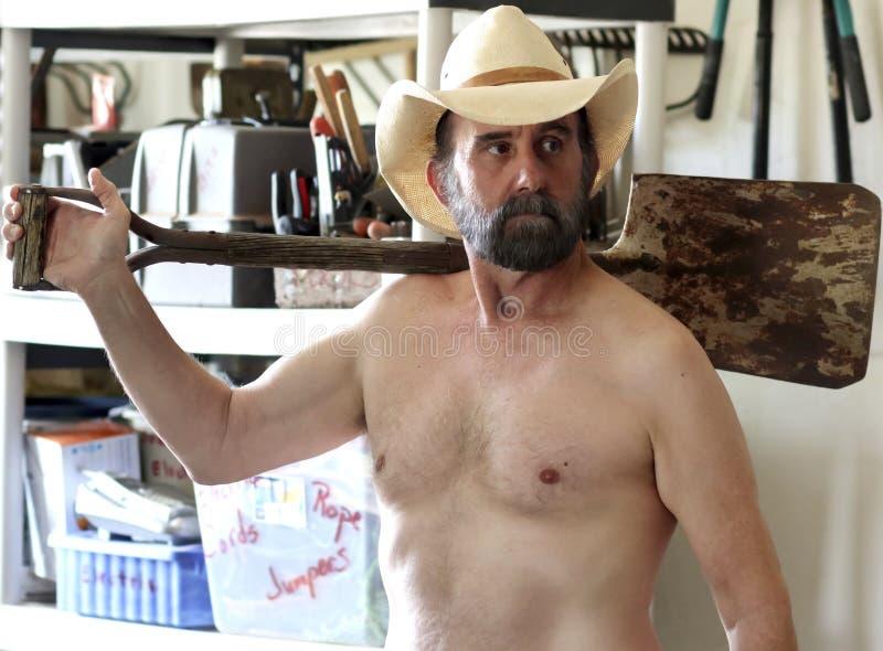 Бородатый ковбой работая лениво в его сарае инструмента стоковое изображение rf