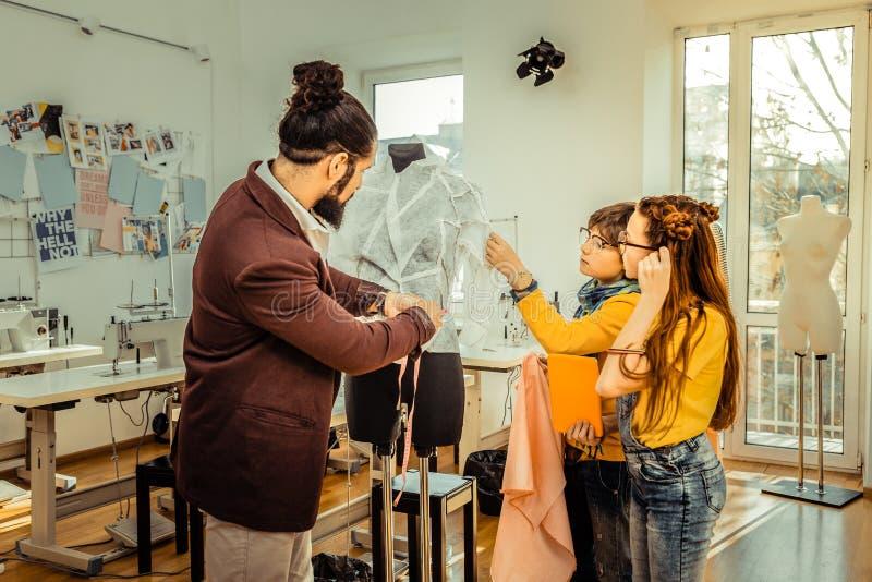 Бородатый модельер показывая его процесс работы к детям стоковая фотография