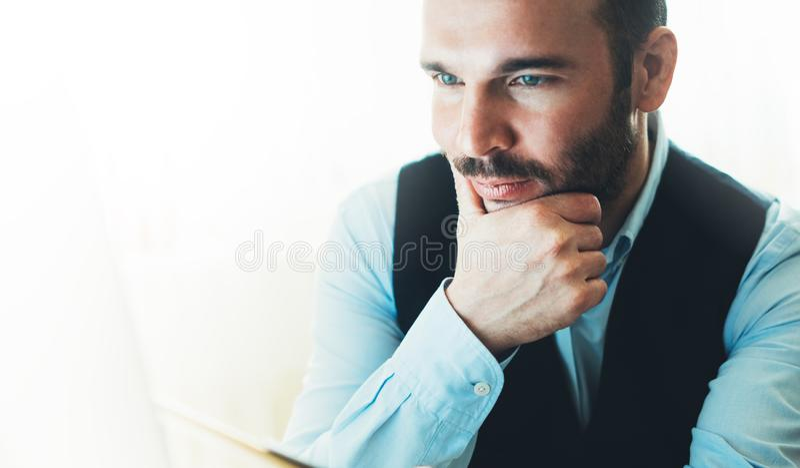 Бородатый молодой бизнесмен работая на современном офисе на ноче Смотреть человека консультанта думая в компьютере монитора Печат стоковые фотографии rf