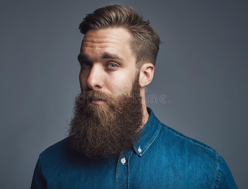 Бородатый молодой хипстер стоя самостоятельно против серой предпосылки стоковая фотография