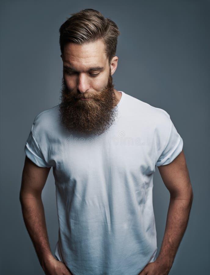 Бородатый молодой человек стоя самостоятельно против серой предпосылки стоковые фото