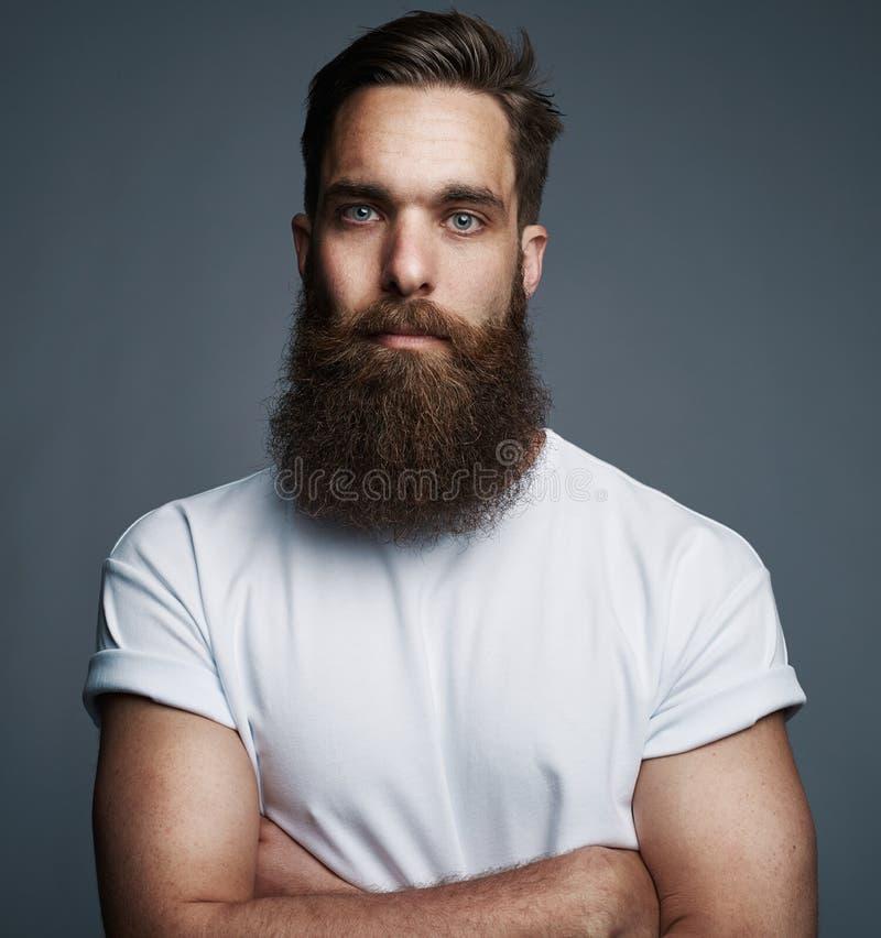 Бородатый молодой человек стоя уверенно с его оружиями пересек стоковые фотографии rf