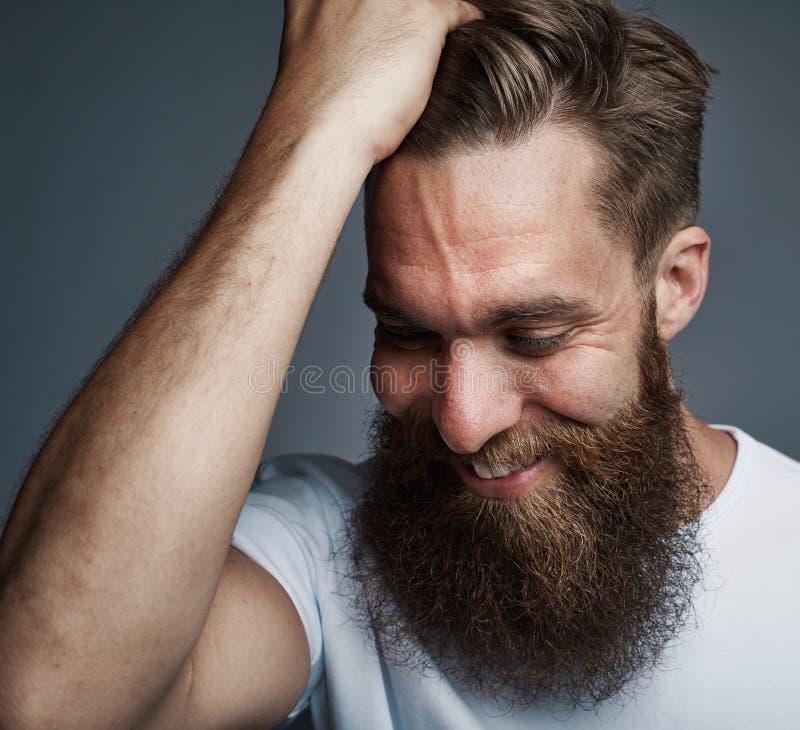 Бородатый молодой человек с рукой в его усмехаться волос стоковое фото
