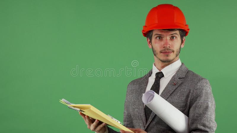 Бородатый мужской инженер смотря смущенный пока читающ документы стоковые фото