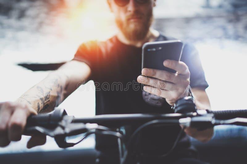 Бородатый мышечный татуированный хипстер в солнечных очках используя смартфон после ехать электрическим скутером в городе стоковое изображение rf