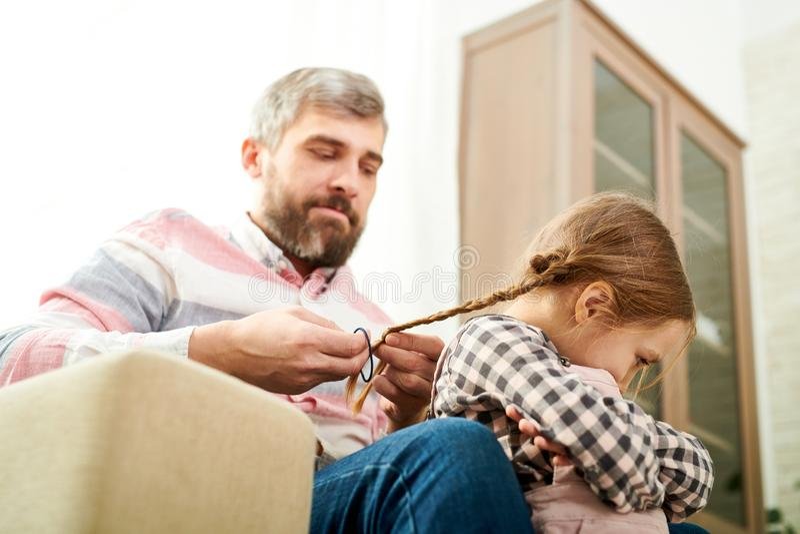 Бородатый отец заплетая маленькую дочь стоковое изображение rf