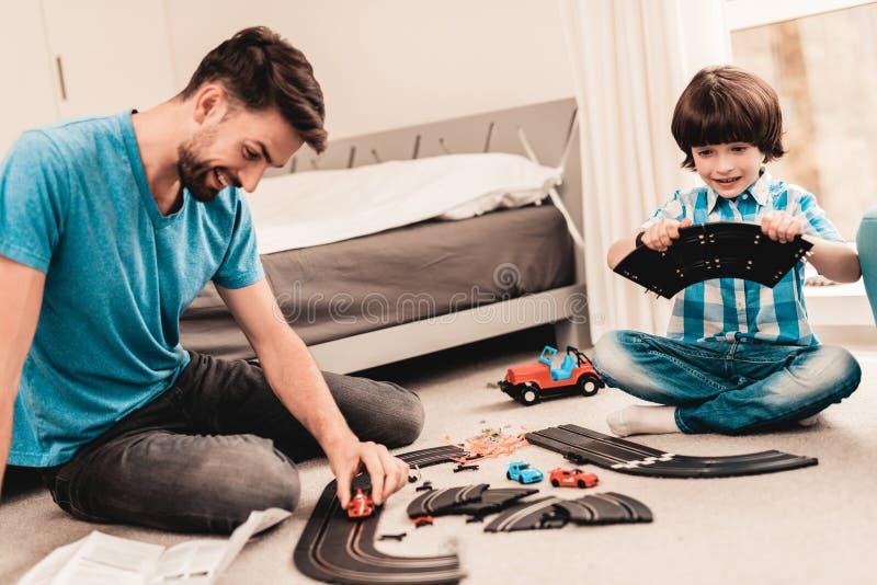 Бородатый отец и сын играя с дорогой гонки игрушки стоковые изображения rf