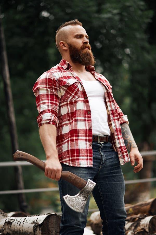 Бородатый работник lumberjack стоя в лесе с осью стоковое фото