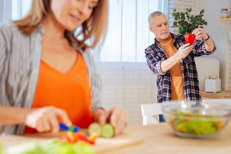 Бородатый супруг держа красный пеец пока помогающ жене стоковые фотографии rf