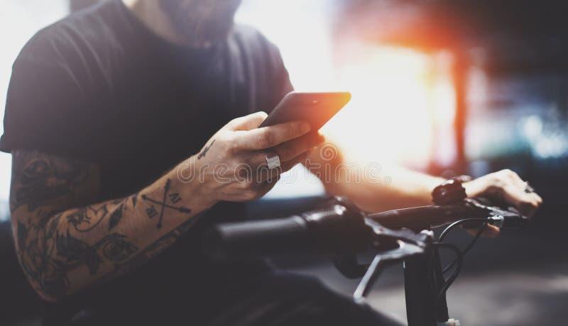 Бородатый татуированный мужчина в солнечных очках используя смартфон после ехать электрическим скутером в городе стоковые фотографии rf
