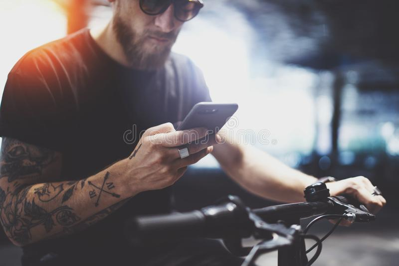 Бородатый татуированный человек в солнечных очках используя мобильный телефон для отправить текстовое сообщение после ехать элект стоковое фото rf