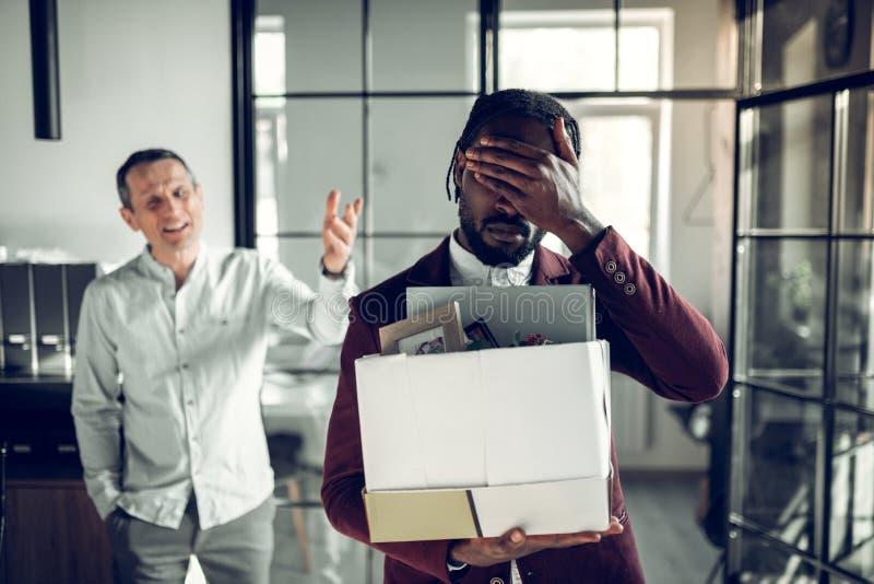 Бородатый темнокожий стажер касаясь его голове после быть увольнятьым стоковые фотографии rf