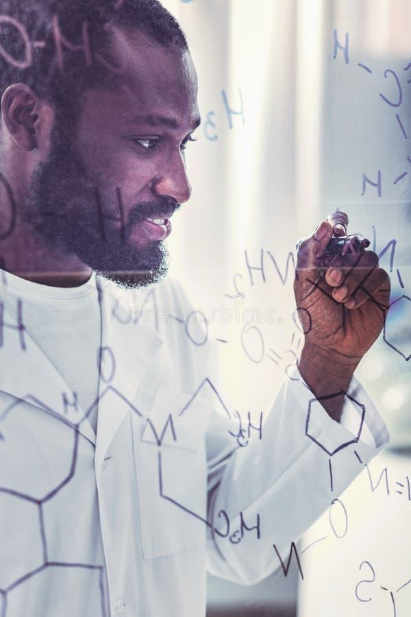 Бородатый усмехаясь химический технолог работая в лаборатории стоковые изображения