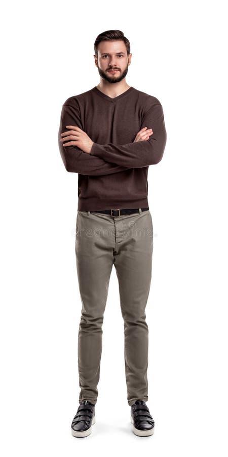Бородатый человек в вскользь наряде стоит в вид спереди с сложенными оружиями и нейтральным выражением стороны стоковая фотография