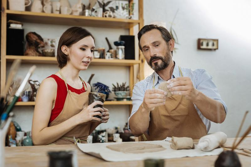 Бородатый человек говоря о делать агашко придает форму чашки его друг стоковые фотографии rf