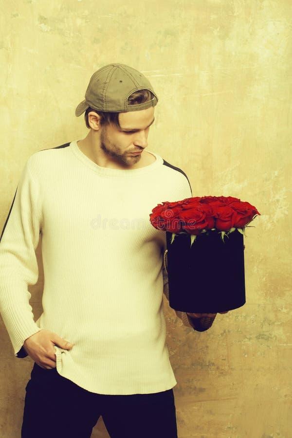 Бородатый человек держит коробку красной розы на текстурированной стене стоковые изображения