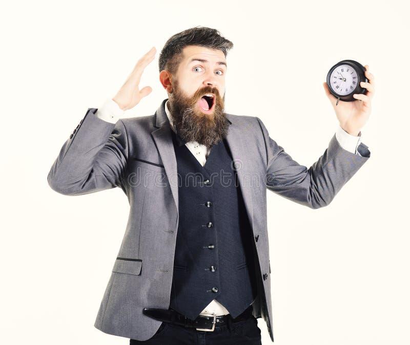 Бородатый человек держит часы и screams Хронометрируйте, слишком занятый, нехватка времени, вечная, спешность, никакое дело време стоковые изображения