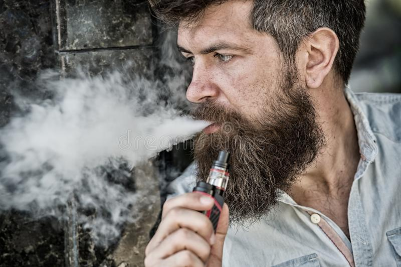 Бородатый человек курит vape, белые облака дыма Электронная концепция сигареты Человек с длинной бородой смотрит расслабленным че стоковое изображение rf
