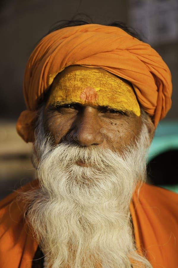 Бородатый человек одетый в апельсине стоковые фото