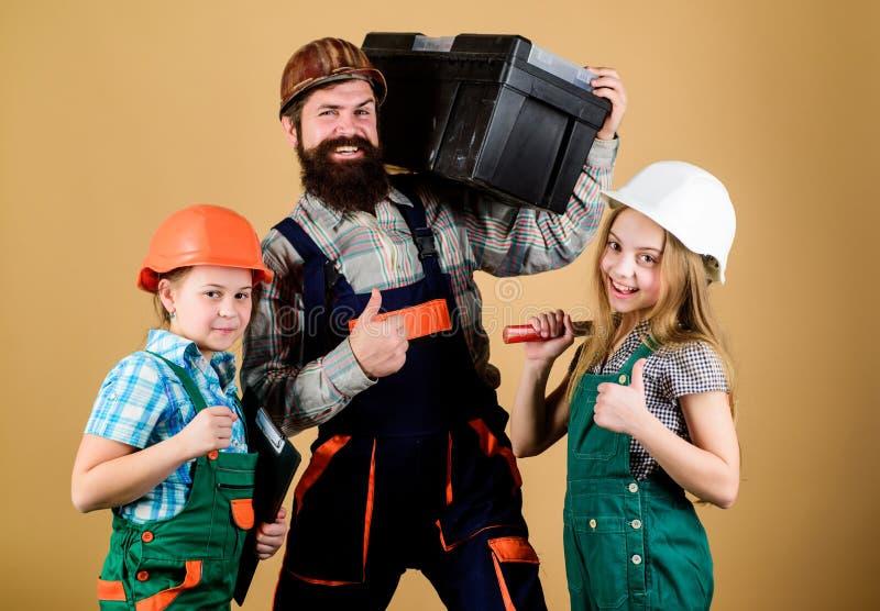 Отец и дочь в мастерской Бородатый человек с маленькими девочками Сыгранность семьи Индустрия Инструменты для ремонта инженерство стоковая фотография rf