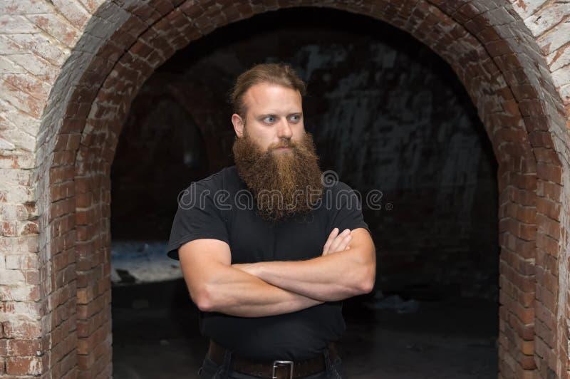 Бородатый человек с пересеченными оружиями, стойками в хмурой комнате под изогнутым сводом стоковая фотография rf