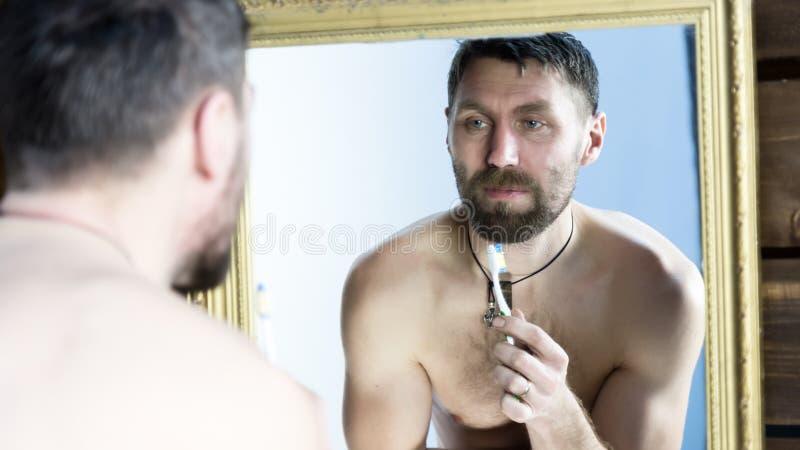 Бородатый человек чистя его зубы щеткой перед зеркалом в ванной комнате стоковые фотографии rf