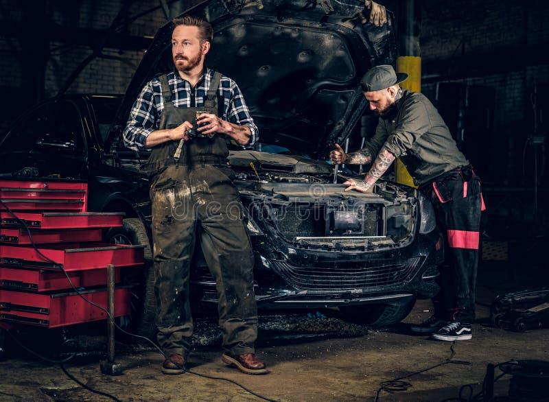 2 бородатых татуированных механика около автомобиля в мастерской стоковое изображение rf
