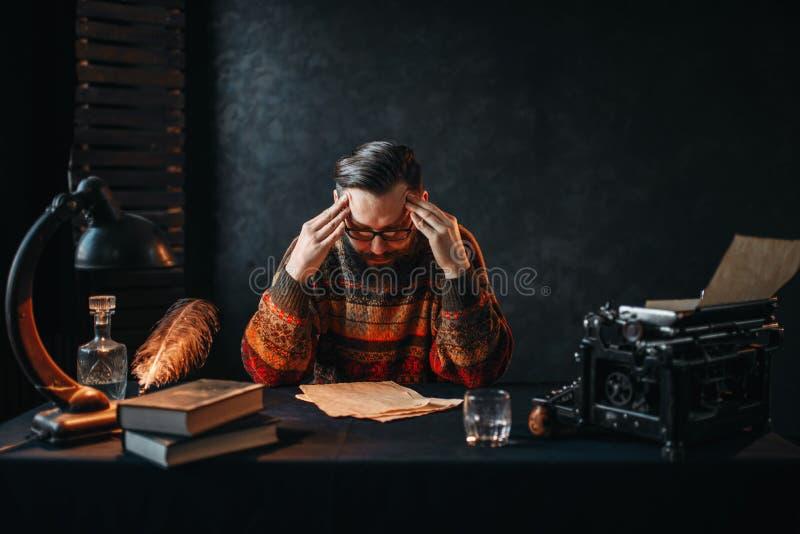Бородатый автор в стеклах читая его работа стоковые фото