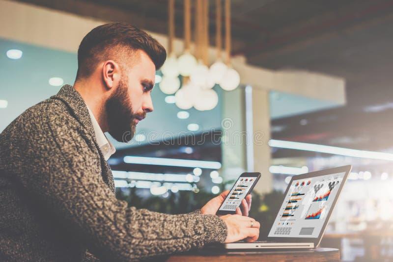 Бородатый бизнесмен сидя на таблице в кафе, держа smartphone и используя компьтер-книжку с диаграммами, диаграммы на экране