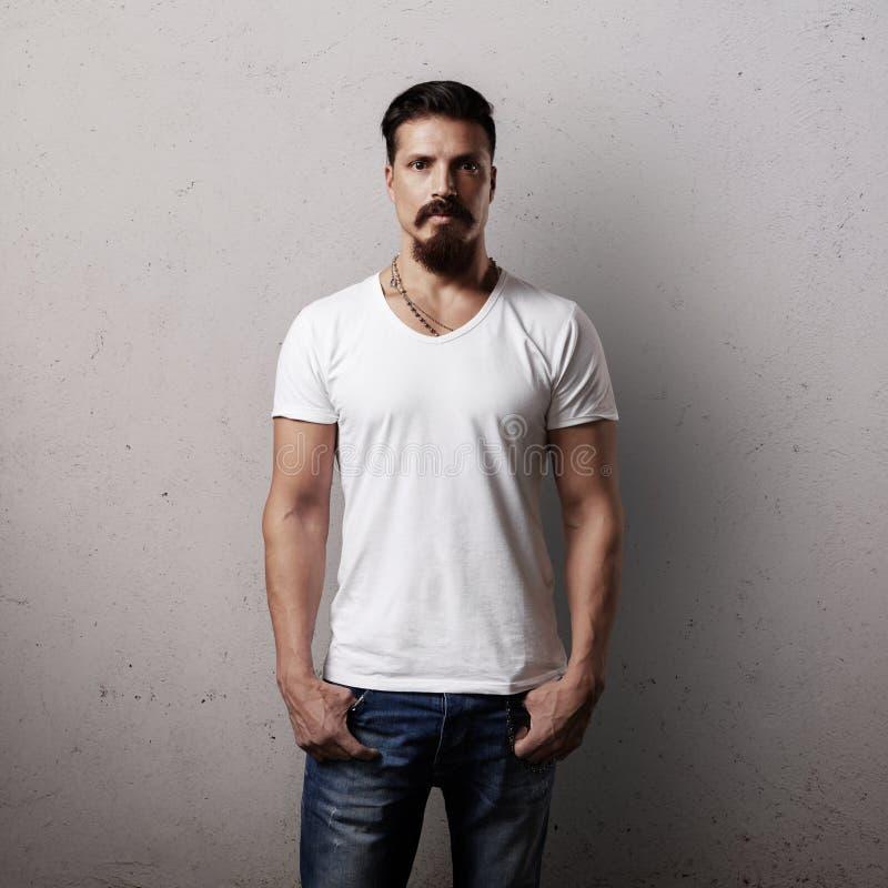 Бородатый красивый парень в белой пустой футболке стоковое изображение rf