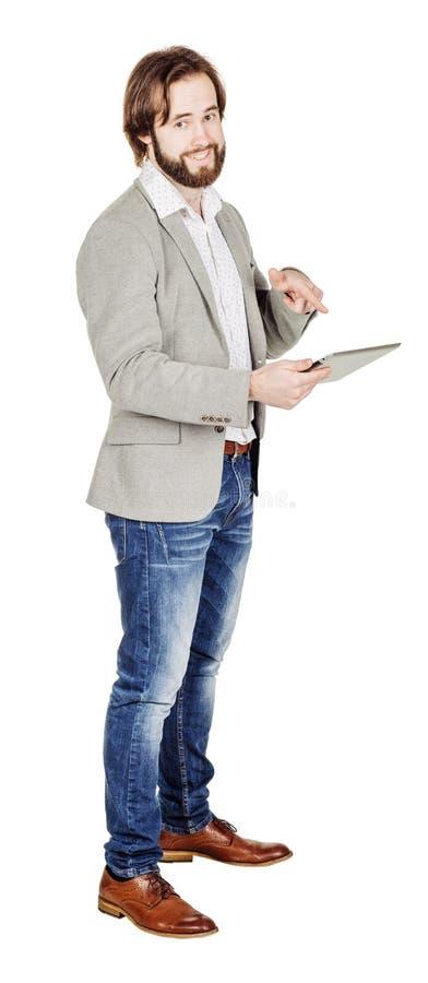 Бородатый молодой бизнесмен используя цифровую таблетку Isolat портрета стоковое изображение
