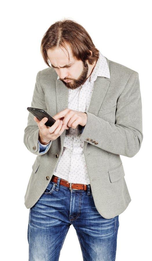 Бородатый молодой бизнесмен используя smartphone o изолированный портретом стоковая фотография rf