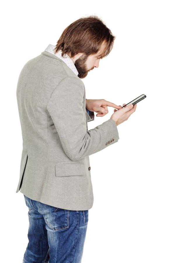 Бородатый молодой бизнесмен используя smartphone o изолированный портретом стоковые изображения