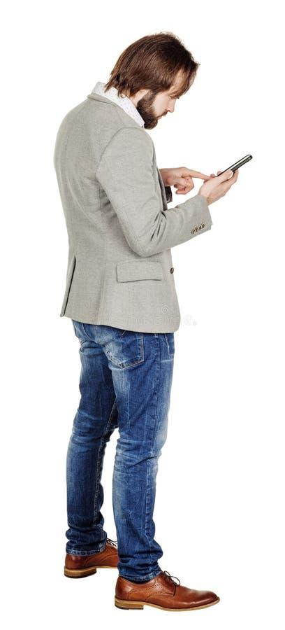 Бородатый молодой бизнесмен используя smartphone o изолированный портретом стоковое изображение rf