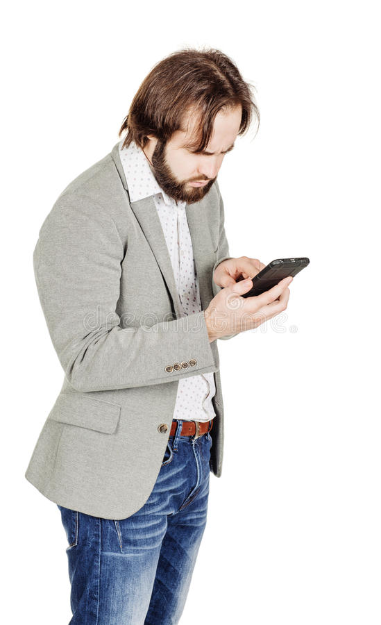 Бородатый молодой бизнесмен используя smartphone o изолированный портретом стоковое изображение