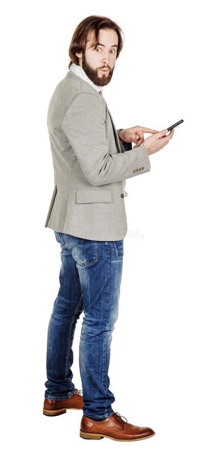 Бородатый молодой бизнесмен используя smartphone o изолированный портретом стоковая фотография