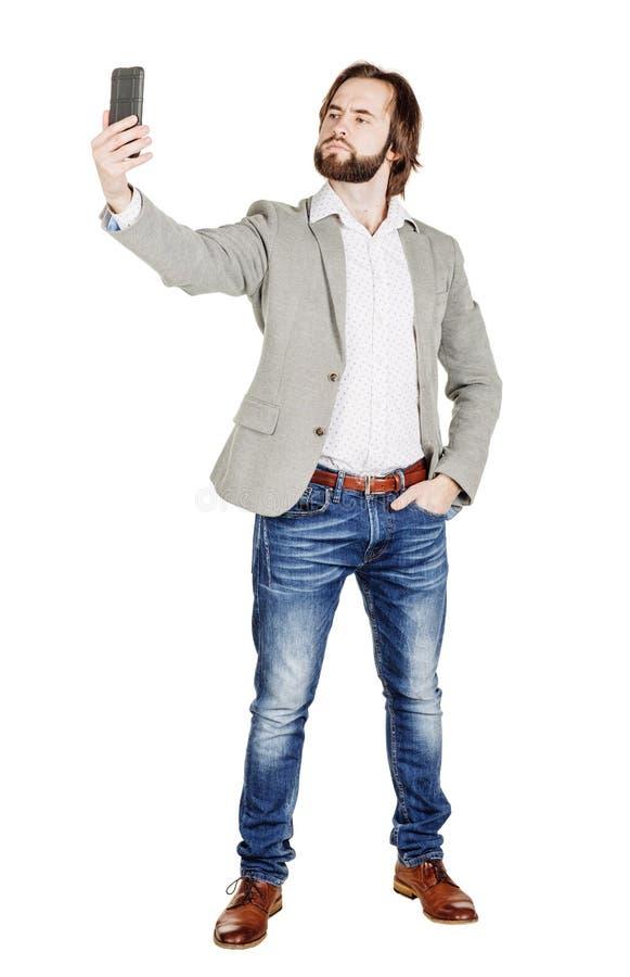 Бородатый молодой бизнесмен принимая усмехаться selfie isola портрета стоковая фотография