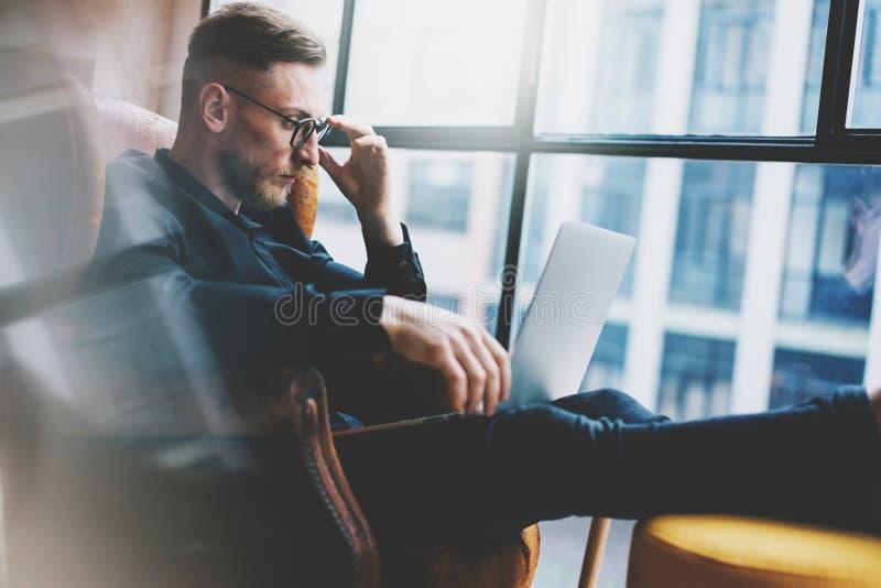 Бородатый молодой бизнесмен работая на современном офисе просторной квартиры Человек сидя в винтажном стуле Используя современную стоковое изображение rf