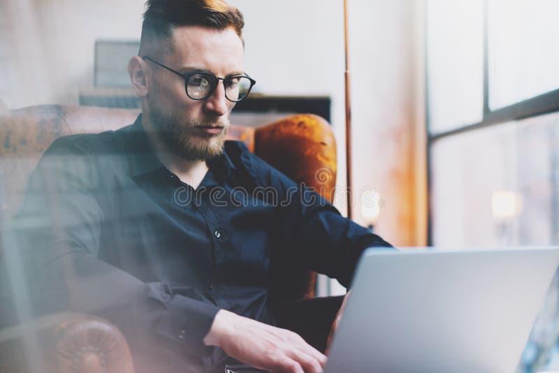 Бородатый молодой бизнесмен работая на современном офисе просторной квартиры Человек сидя в винтажном стуле Используя современную стоковые фотографии rf