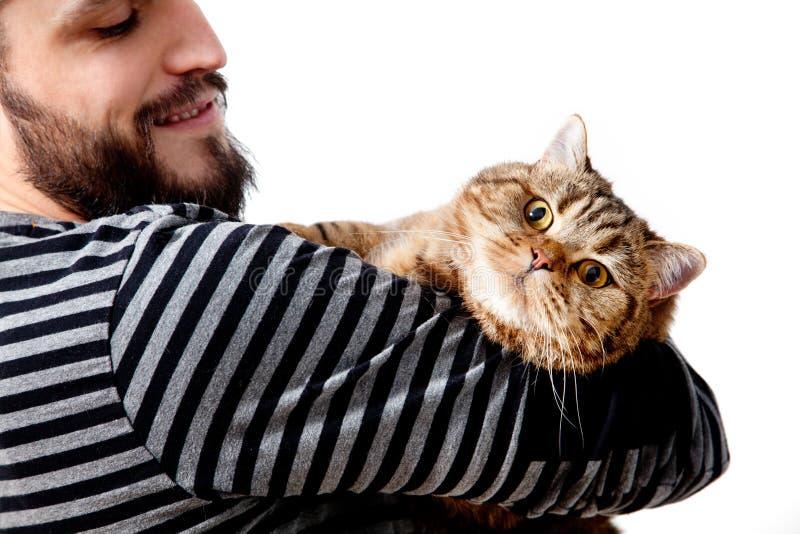 бородатый молодой человек обнимая его красивого кота на белой предпосылке стоковая фотография rf