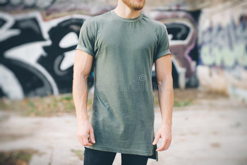Бородатый парень нося зеленую пустую футболку и черные джинсы, стоя на улице стоковое изображение